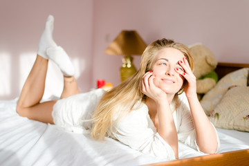 young woman lying in bed in sunlight happy smiling