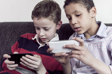 two boys playing a game on a smartphone