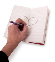 hands drawing hart in blank notebook on table
