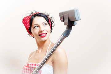 beautiful young pinup woman with vacuum cleaner