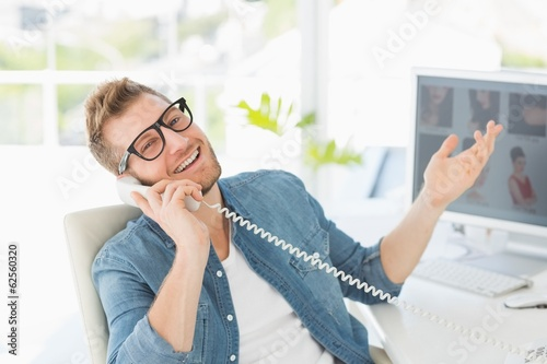 Handsome designer laughing on the telephone looking at camera