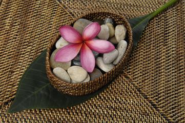 Single frangipani with stones on burlap texture