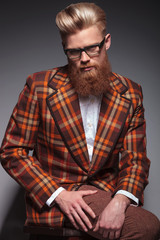 dramatic fashion model with long beard and glasses sitting