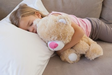 Girl sleeping on sofa with stuffed toy