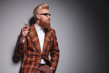 side view of a cool fashion man with great hairstyle smoking