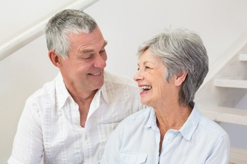 Senior couple sitting on stairs smiling at each other