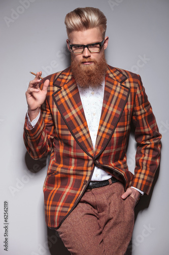 serious fashion man with beard and nice hairstyle smoking