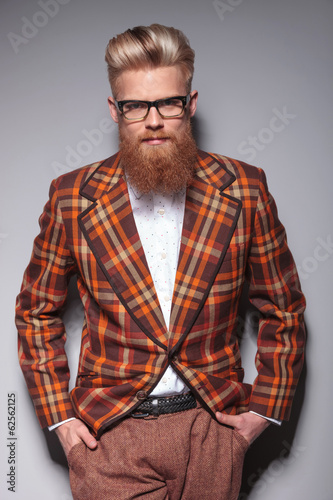 smiling fashion model with long beard leaning against gray wall