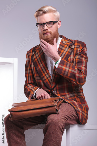 fashion man sitting and playing with his long beard