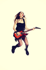 Girl with electric guitar is playing and jumping.