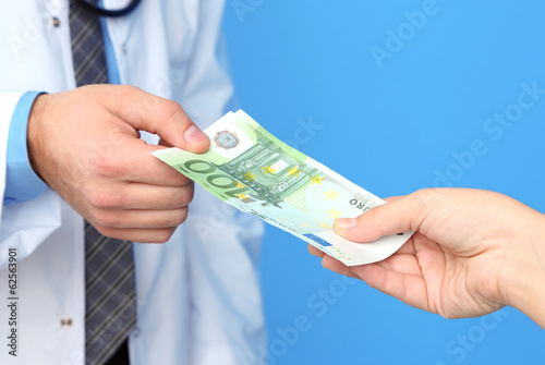 Male Doctor receiving money from patient, on blue background