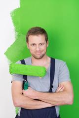 handwerker mit verschränkten armen vor grüner wand