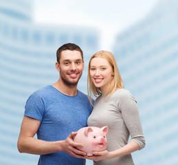 smiling couple holding big piggy bank