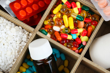 Medical pills, ampules in wooden box, close-up