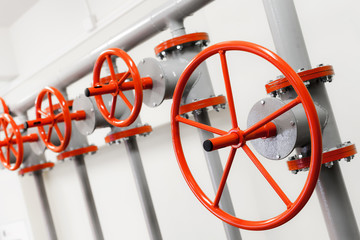 Group of red industrial valves on pipeline system