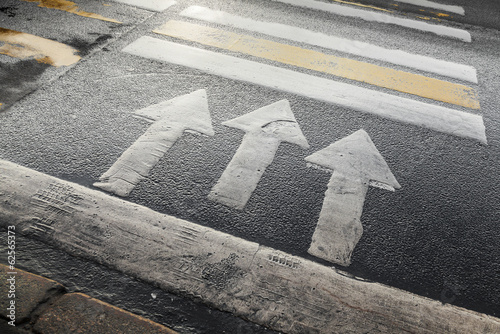 Pedestrian crossing road marking with arrows on asphalt