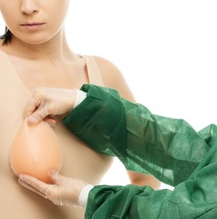 Plastic surgeon trying on breast implant on client