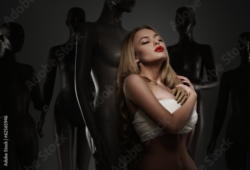 Young woman in bandage among mannequins