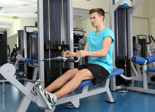 Young man training with weights in gym