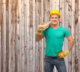 smiling manual worker in helmet with wooden boards