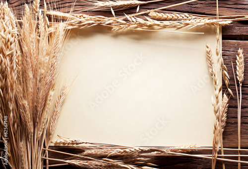 Ears of wheat in the form frame on old wooden table.