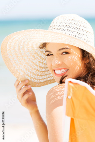 Woman in a hat and swimsuit over seaside sunny day.