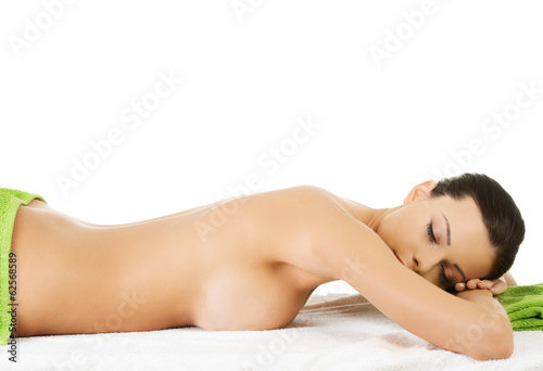 Woman lying at spa salon.