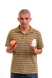 Man offering pill in one hand and apple in another. Copy space b