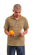 The right choice. young man holding an orange in one hand and pi