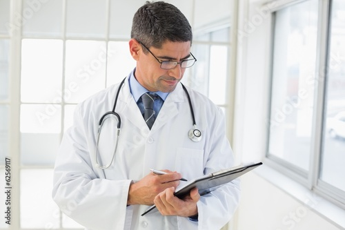 Serious male doctor writing reports