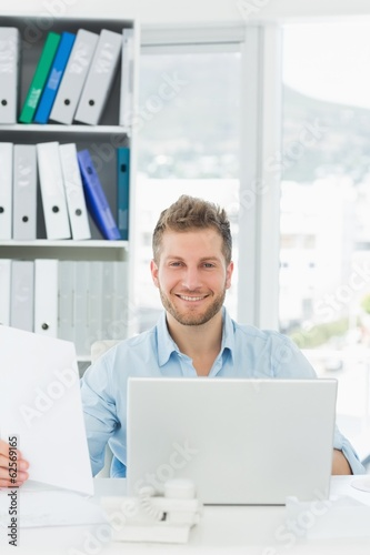 Handsome man working at his desk smiling at camera