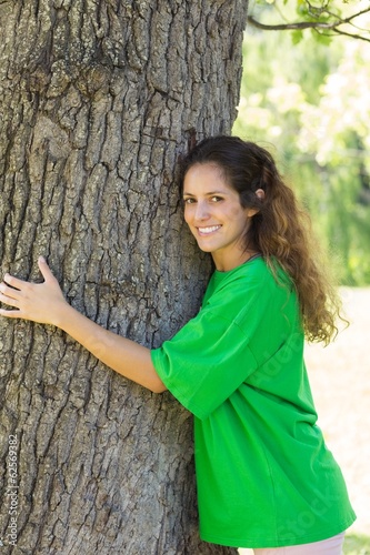 Environmentalist embracing tree trunk