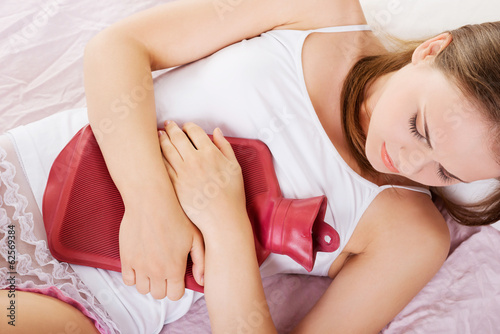 Woman lying in bed with hot water bag