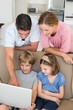 Parents teaching children to use laptop
