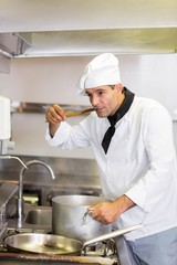 Male cook tasting food in kitchen