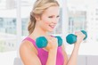 Happy blonde lifting dumbbells