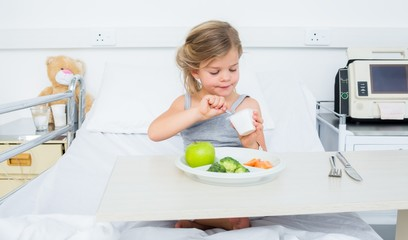 Ill girl eating healthy food in hospital