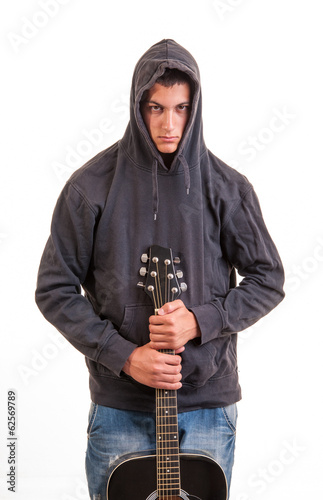 A young boy in hoodie standing and holding his guitar