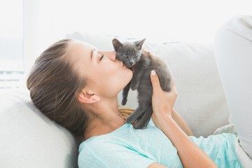 Cheerful woman lying on sofa kissing a grey kitten