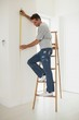 Full length of a man on ladder while measuring wall