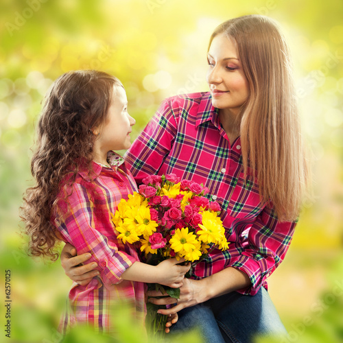Daughter hugging his mother and gives her flowers