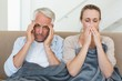 Sick couple sitting on the couch under a blanket