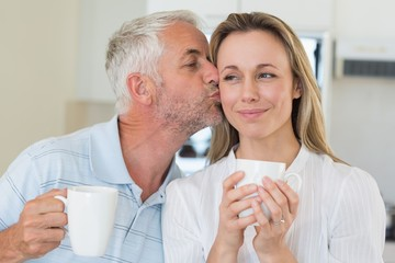 Smiling man giving his partner a kiss on the cheek