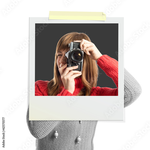 Girl taking a picture inside photo frame over white background
