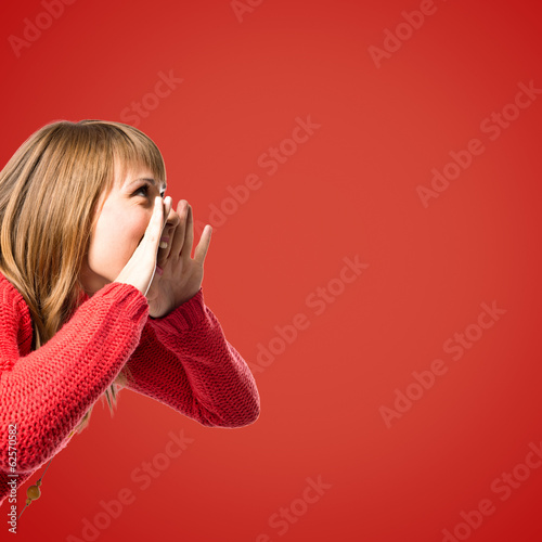Young girl shouting over red background