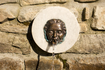 wood fountain in the form of iron masks