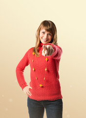 Young pretty woman pointing over ocher background