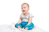 Cute baby boy sitting on a white blanket isolated on white