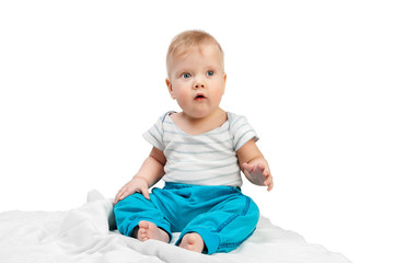 Cute little boy sitting on a white blanket isolated on white