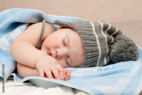 Cute sleeping boy in hat with pompom